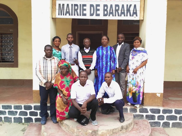 In-person gatherings held according to safety measures required by the government. The members of the Bahá'í Local Spiritual Assembly visiting the vice-mayor of Baraka, Emerite Tabisha (standing third from right).