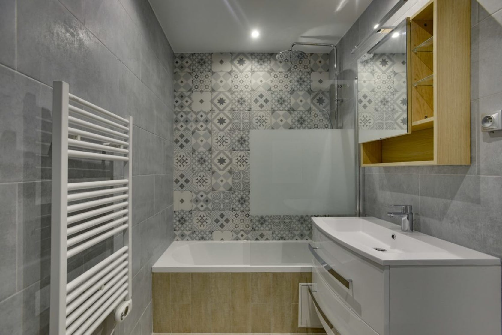 Carrelage mural, baignoire rectangulaire et vasque meuble.