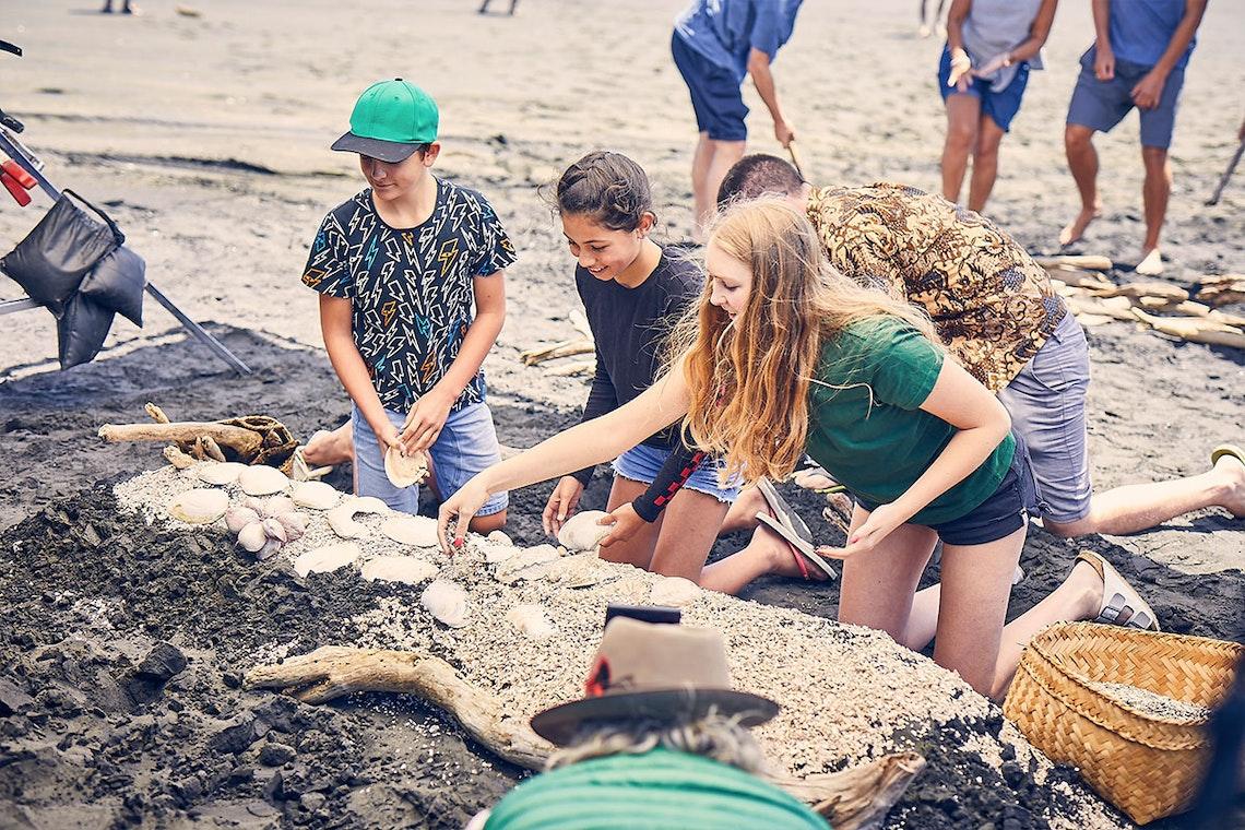 solarZero staff, friends and whanau create a koru on the beach