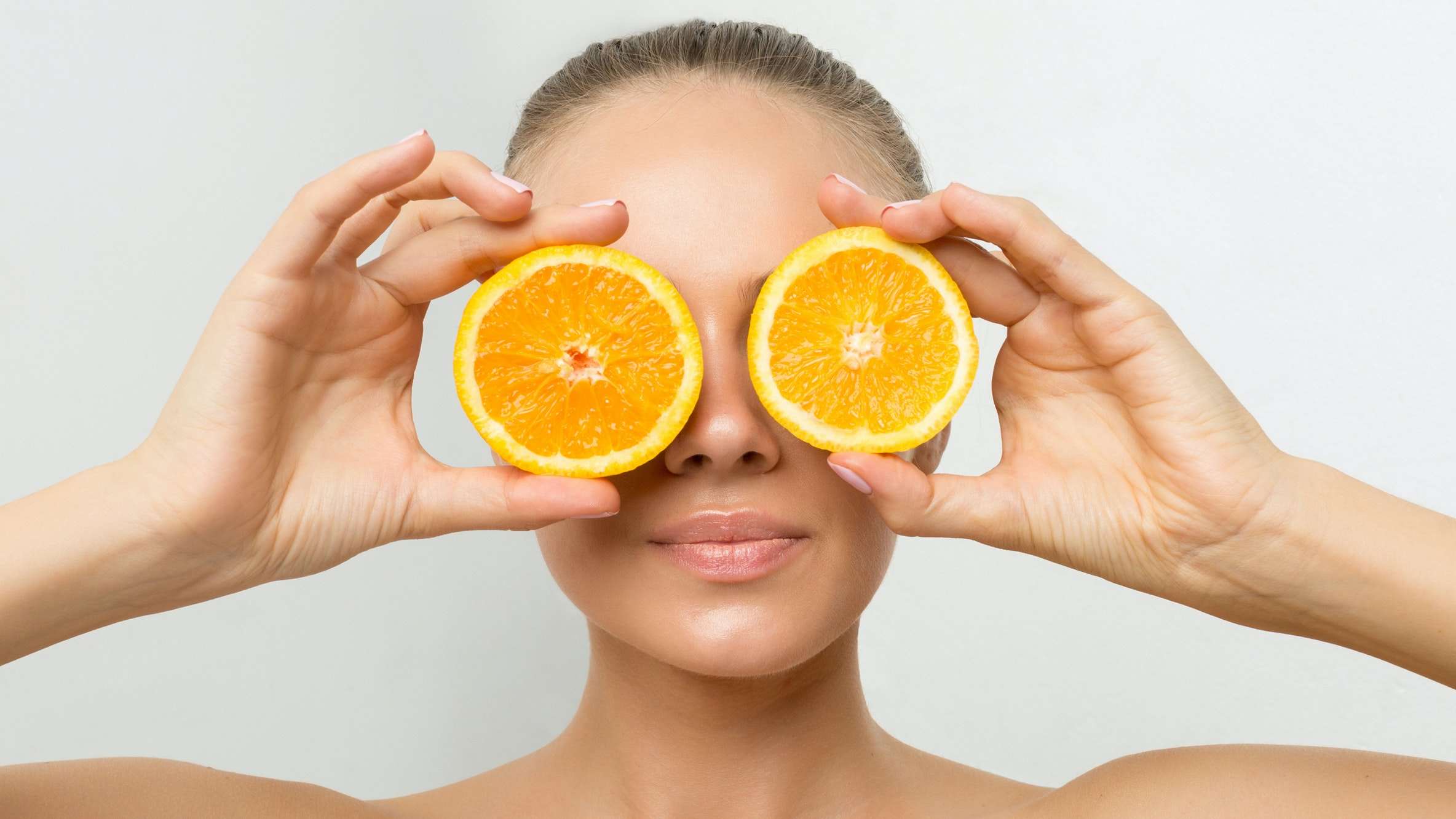 woman with two orange slices over her eyes