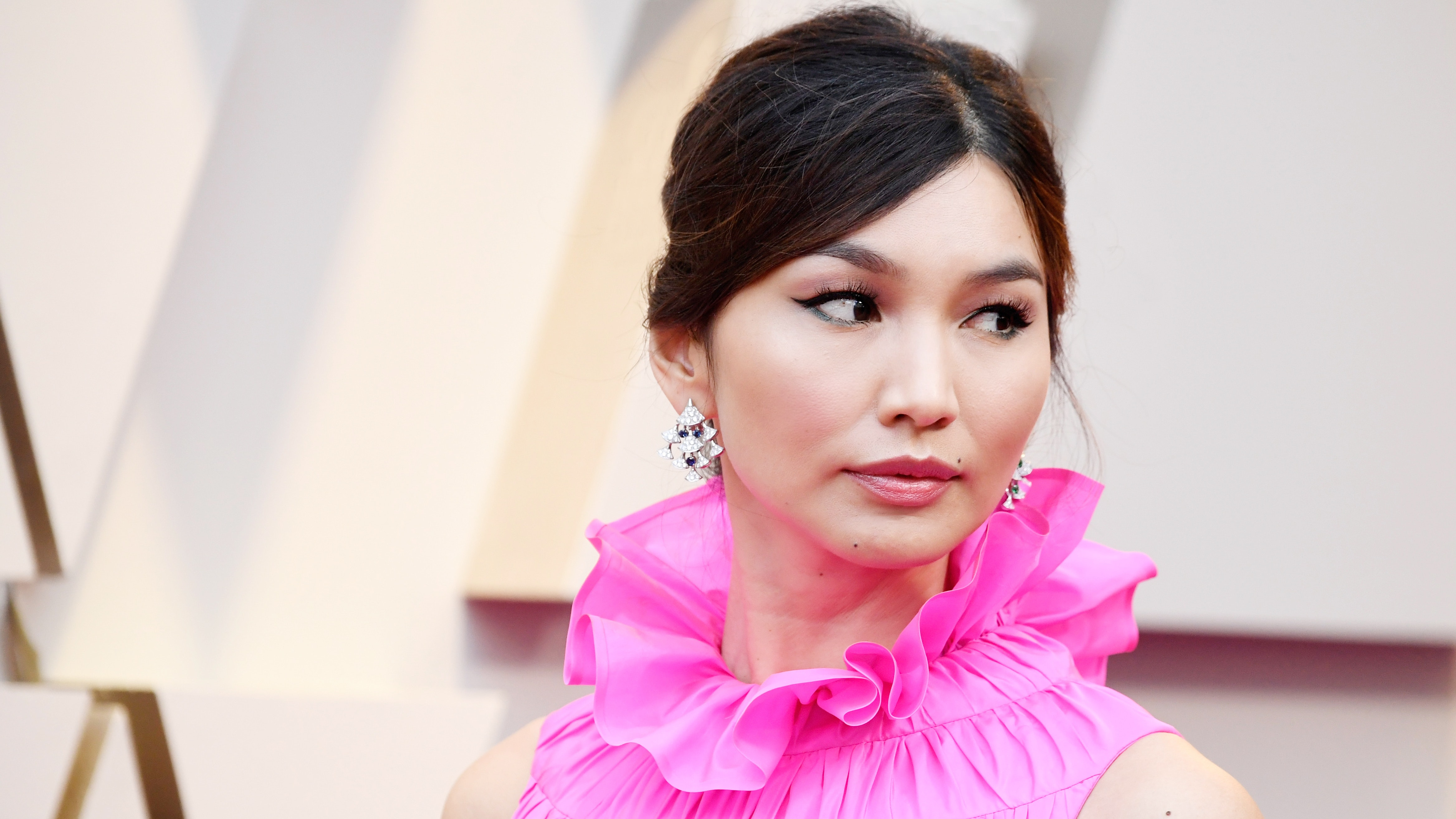 Gemma Chan walks the red carpet in a pink dress.