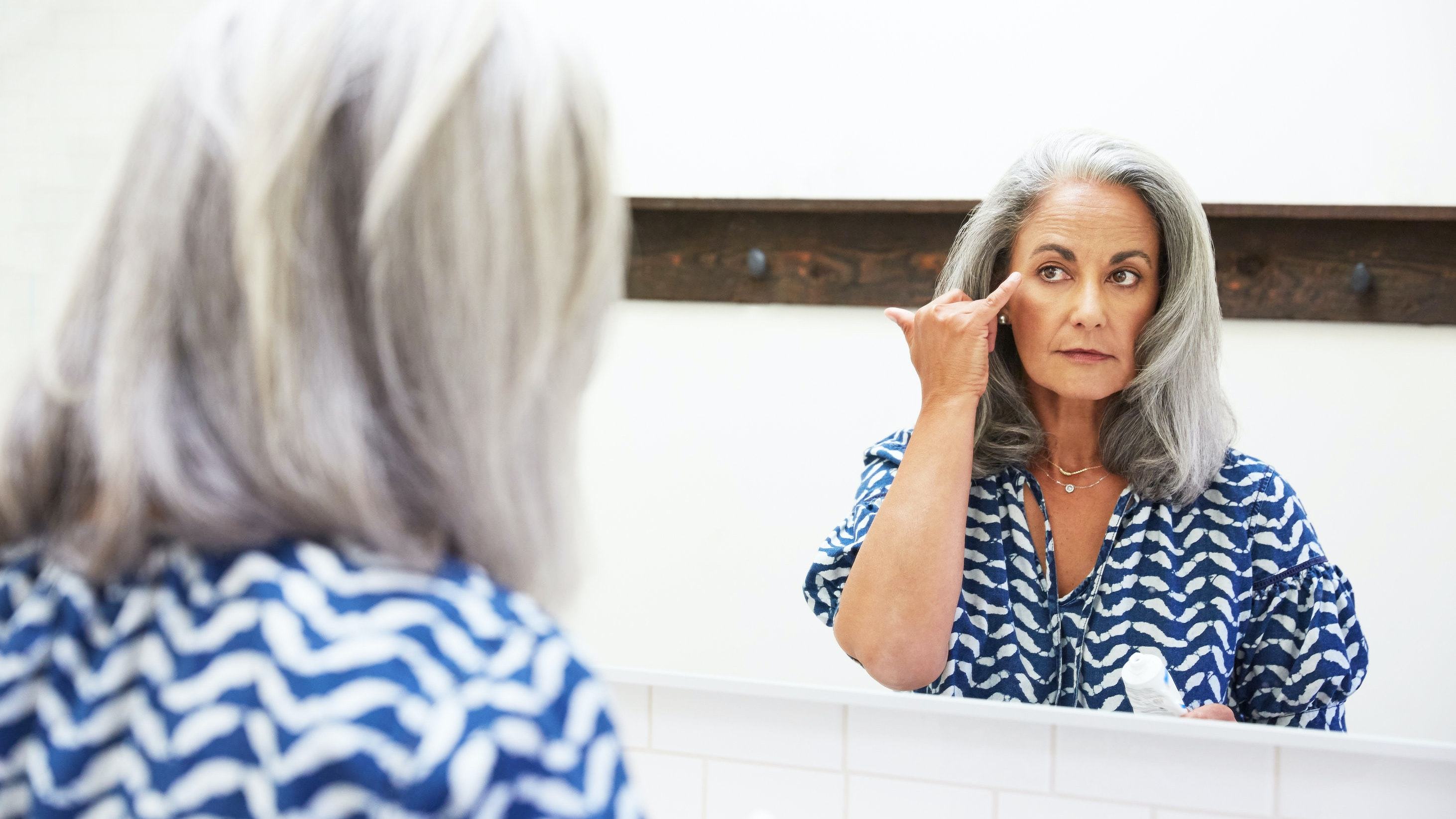 Women looks at her wrinkles in the mirror.