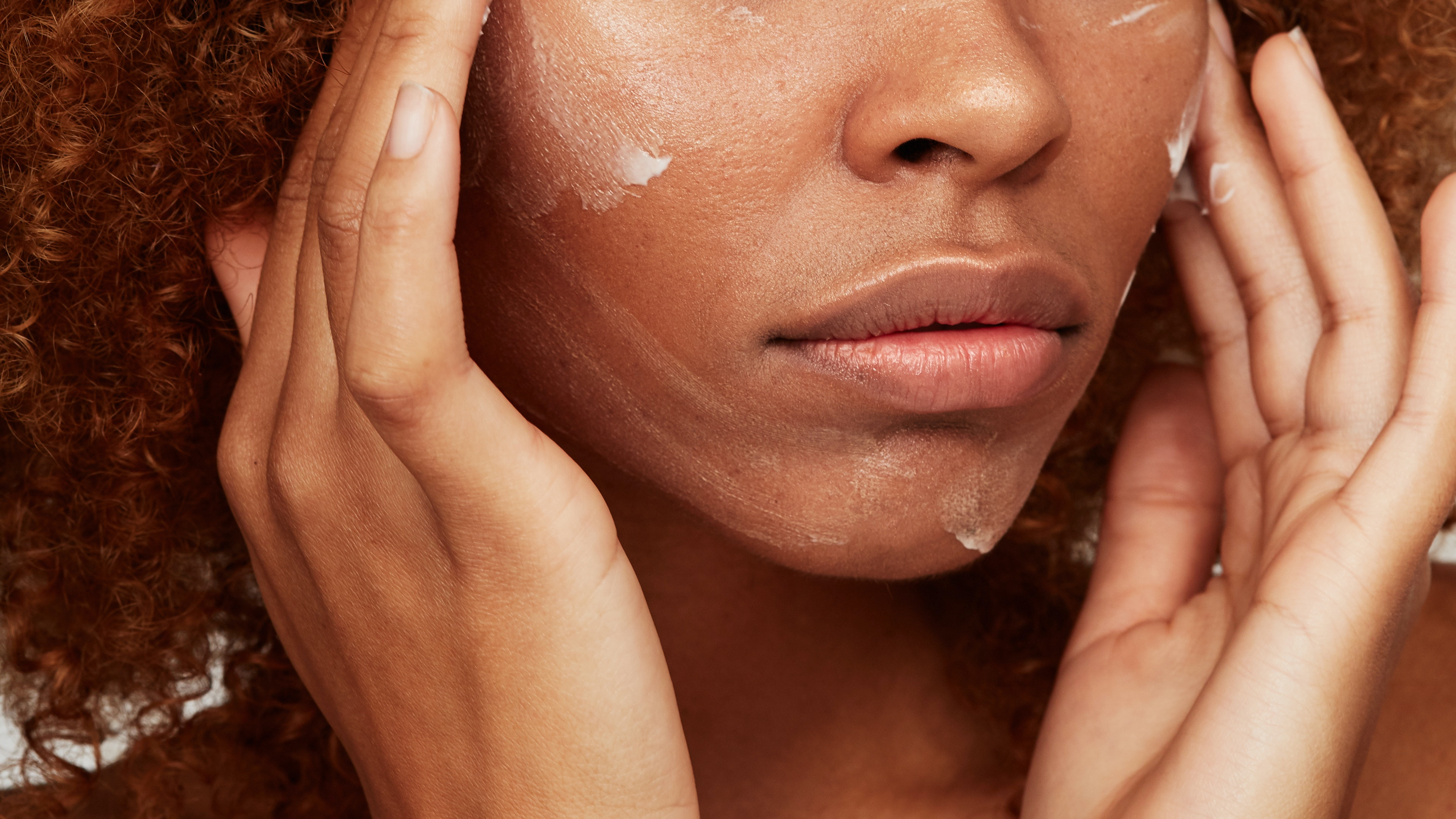 Black woman putting on white face cream.