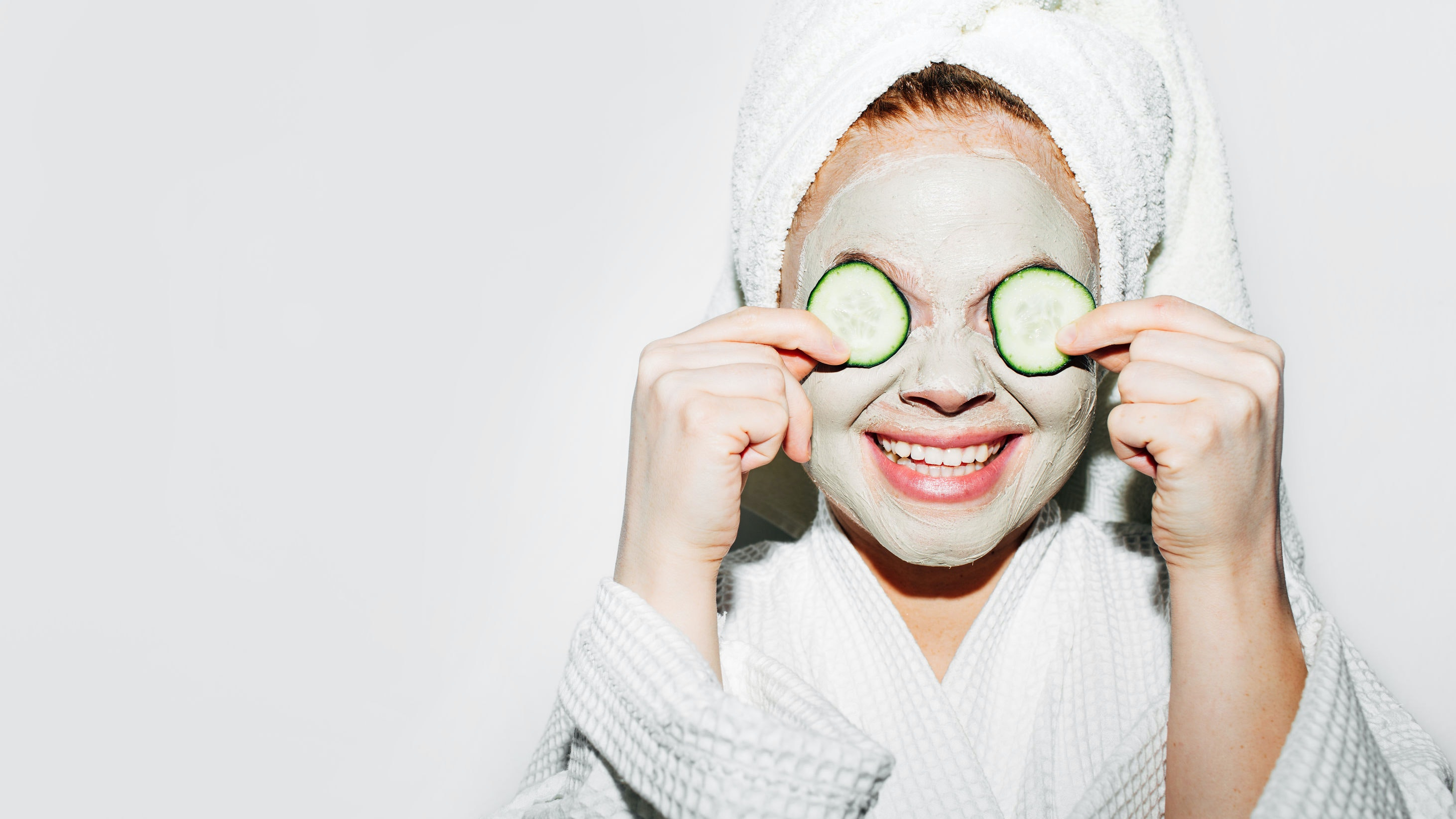 Woman putting cucumbers on her eyes