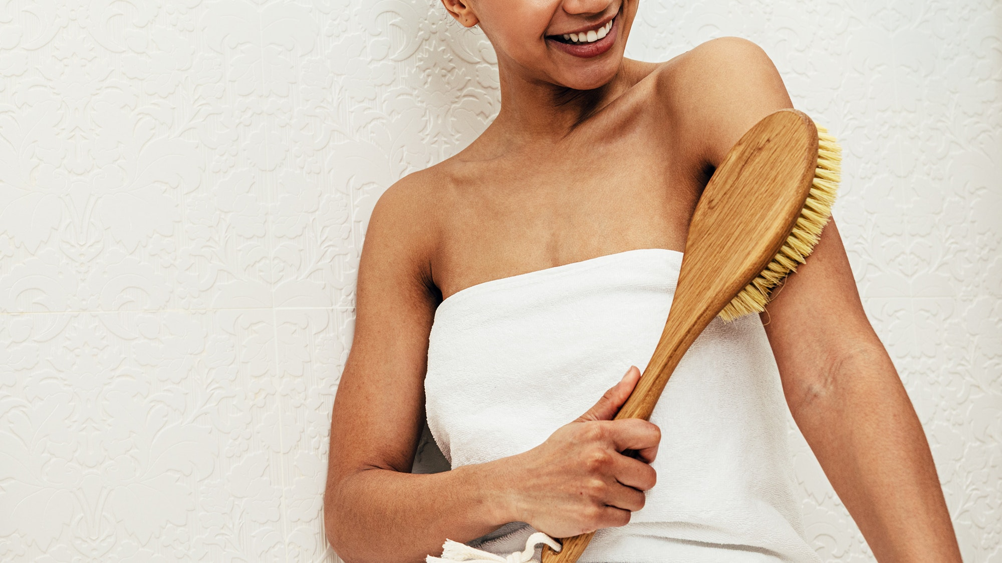 Woman dry brushing skin