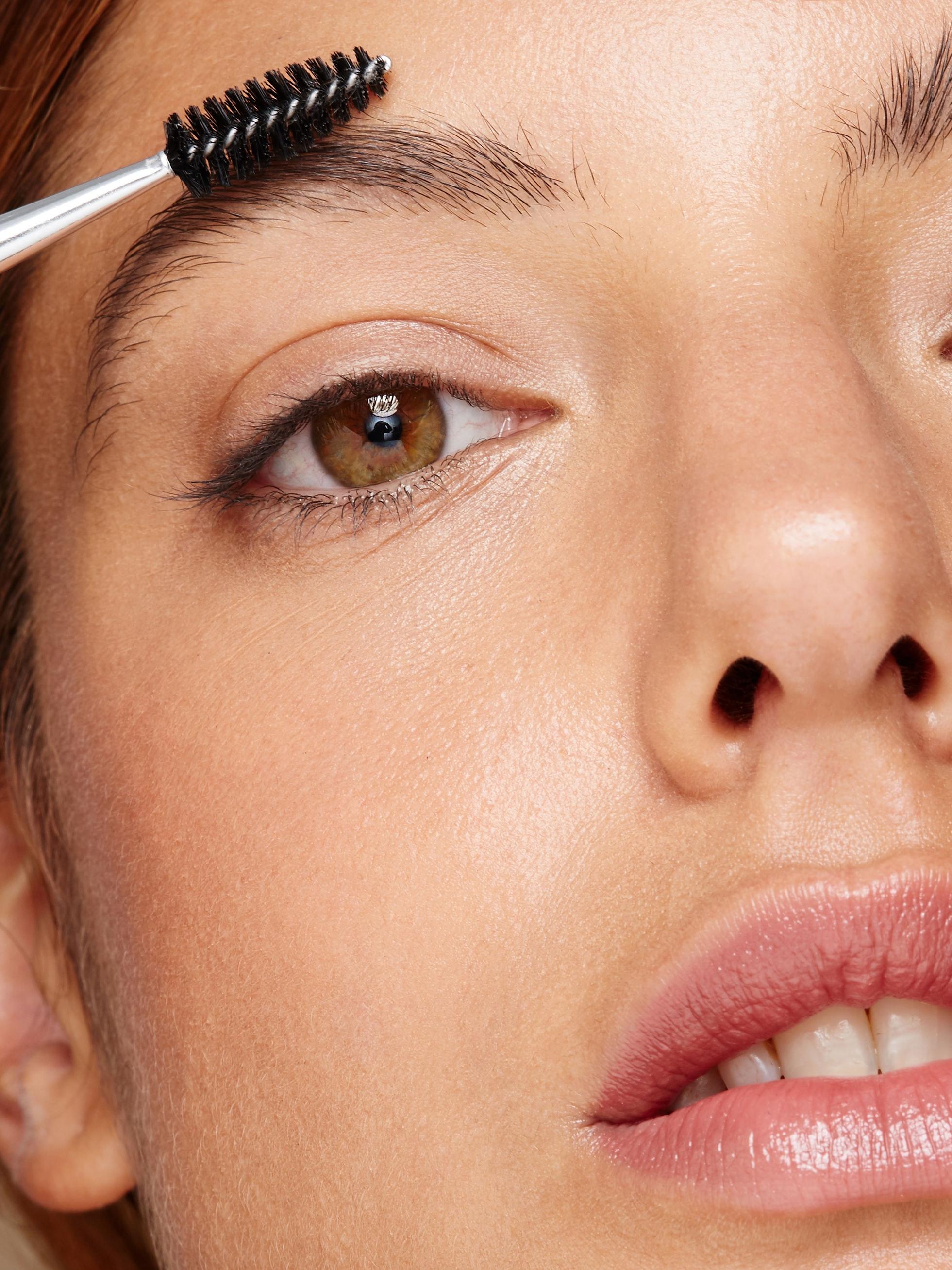 Woman grooming her eyesbrows