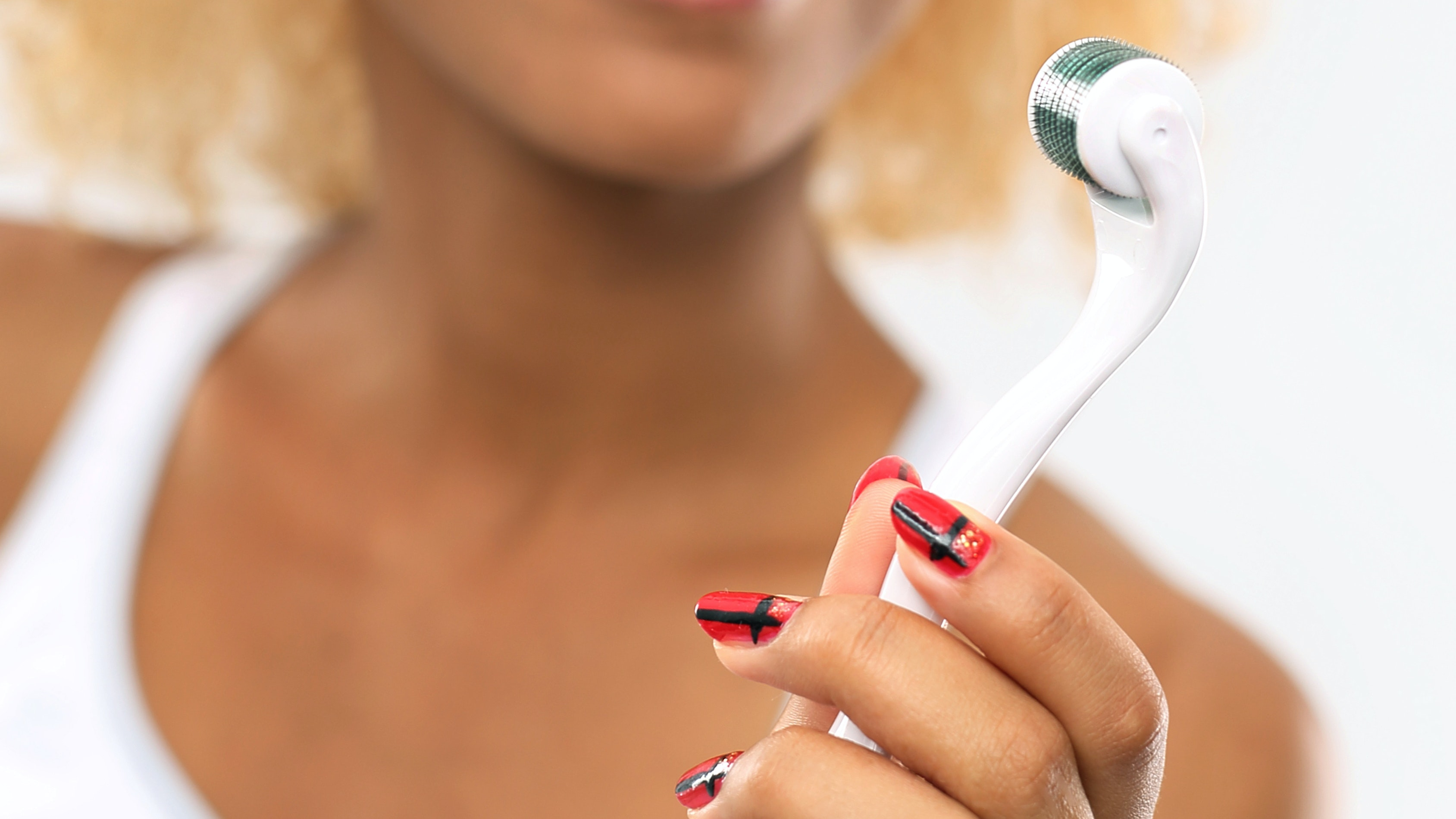 Woman holding a microneedling tool