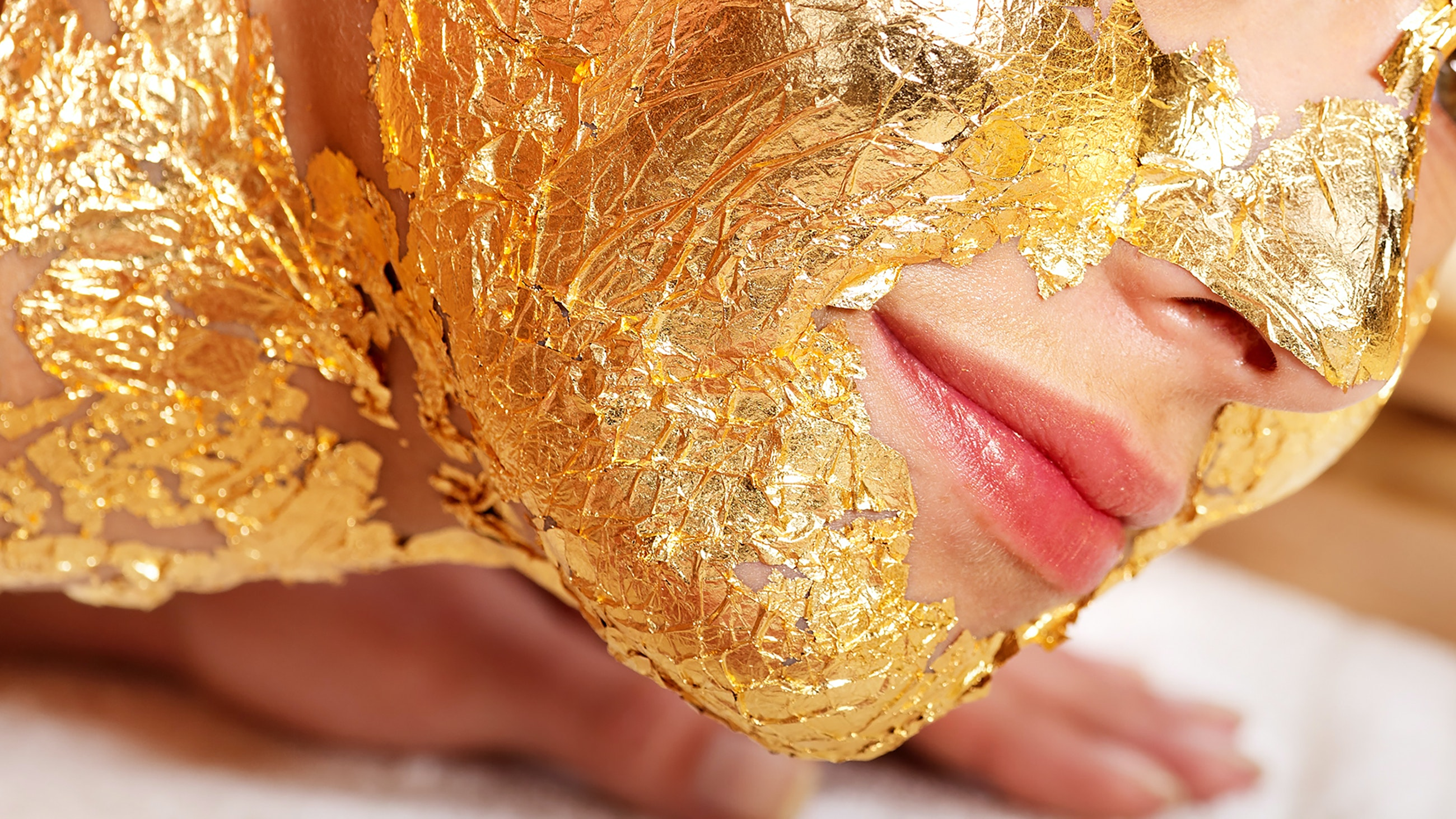 Woman getting face painted in gold