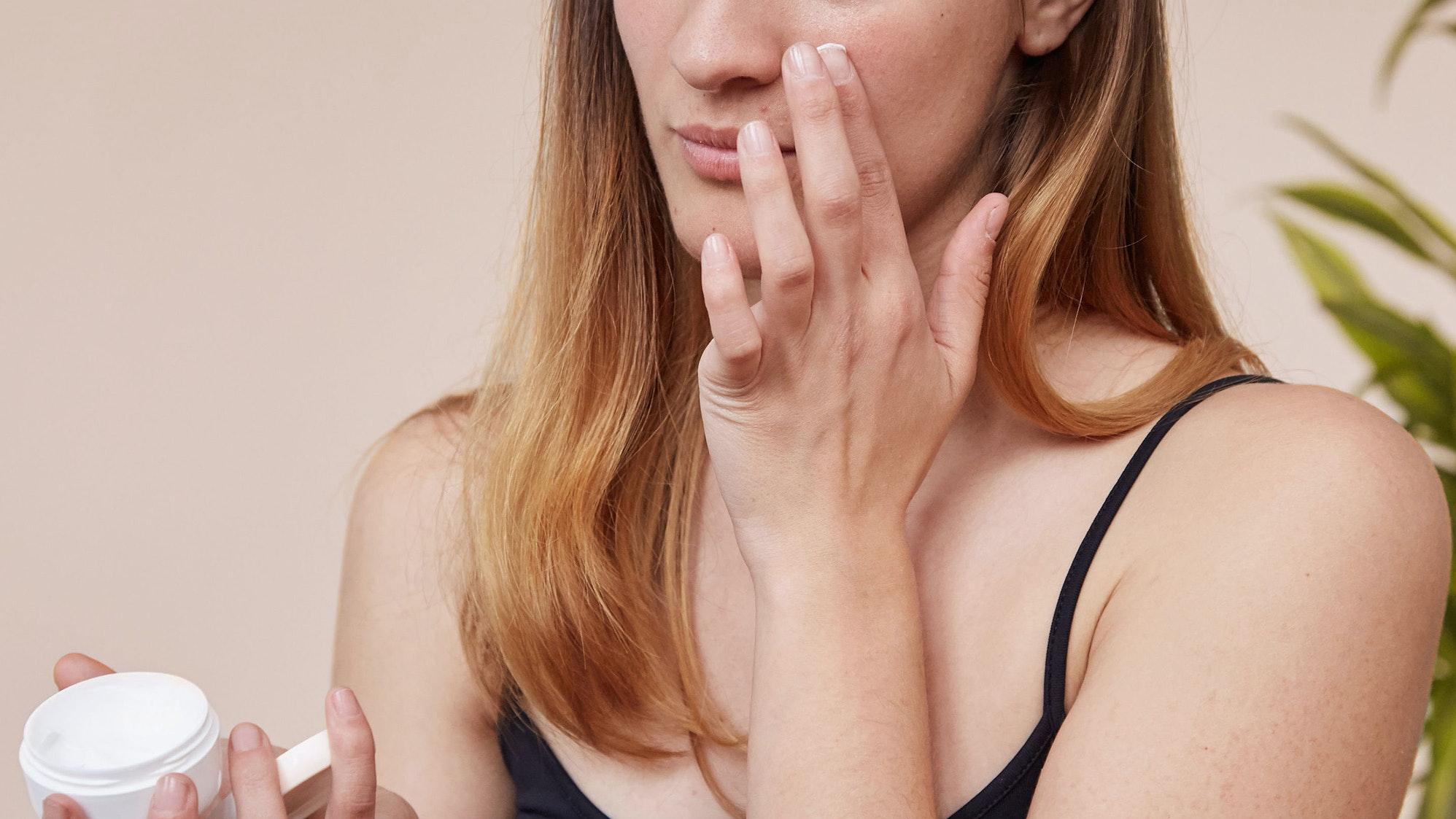 woman applying pimple cream