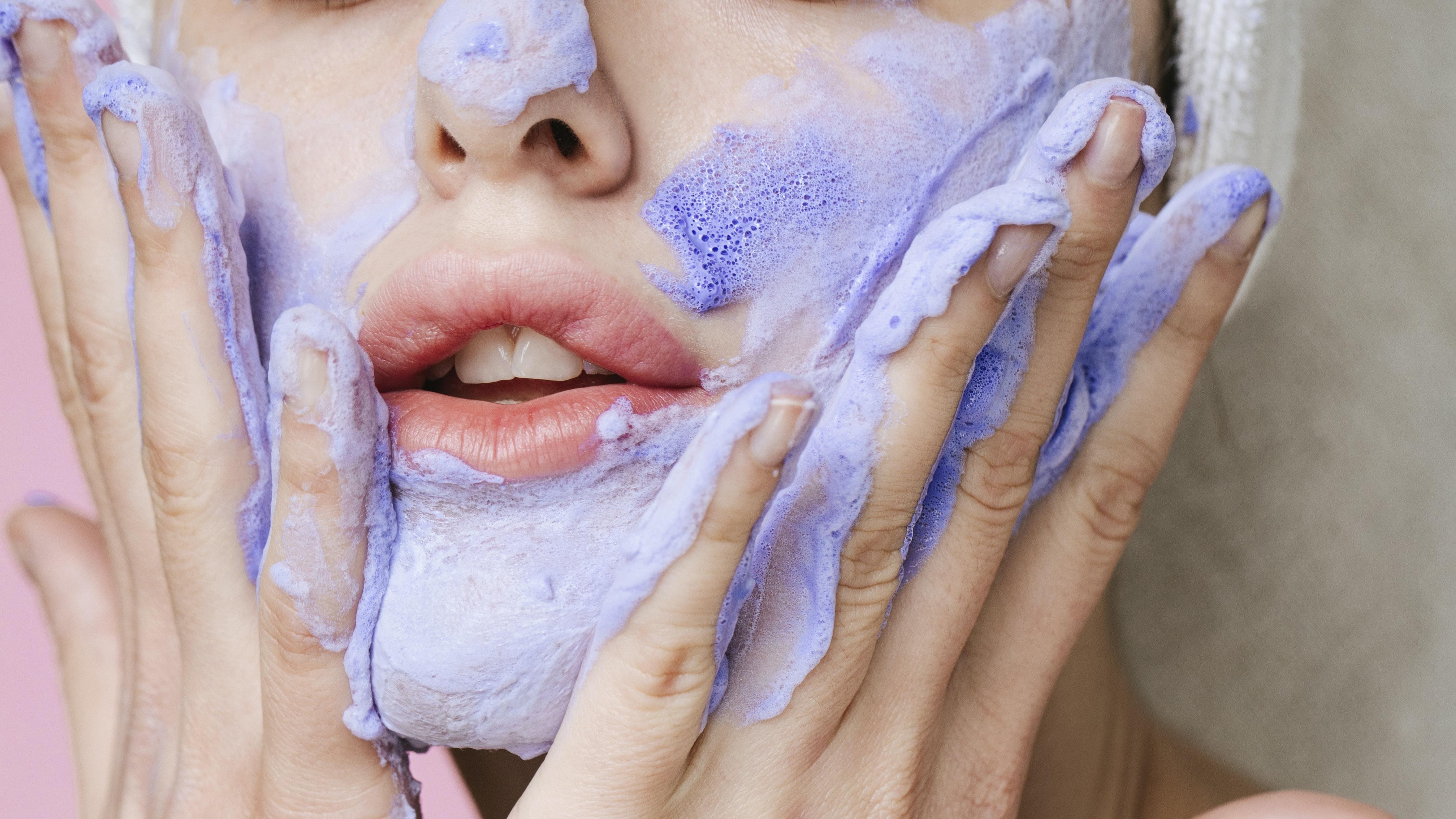 woman applying purple skincare mask