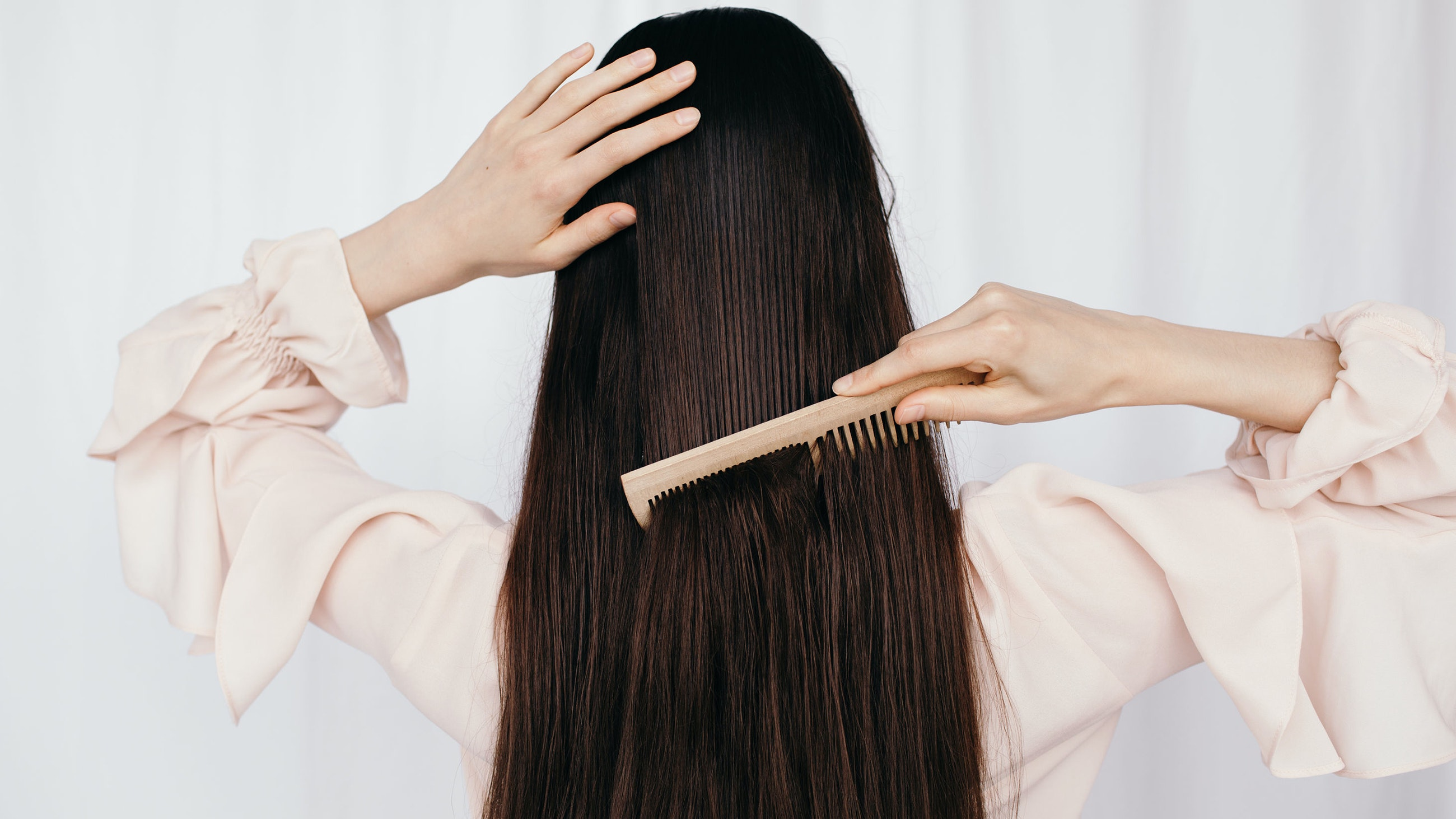Woman brushing long brown hair
