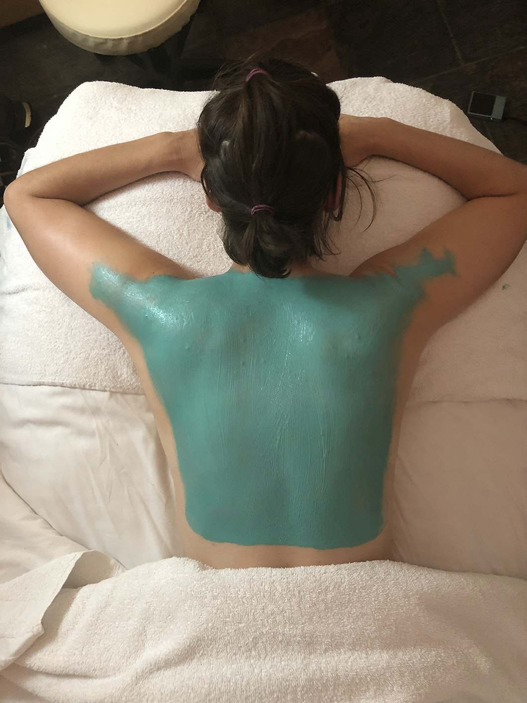 woman with green body mask on her back