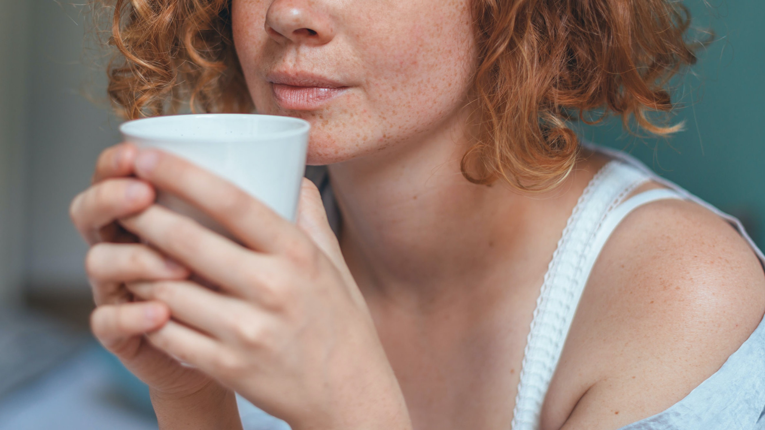 Woman with red hair drinking from cup