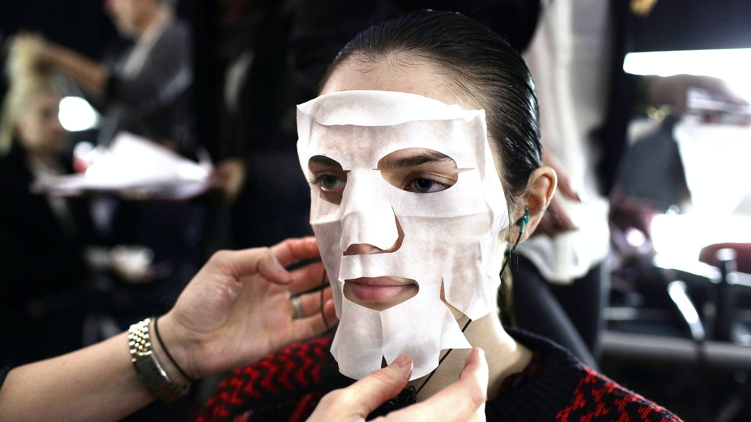 A model has moisturizer mask applied to her face backstage before presenting a creation by Carolina Herrera Fall/Winter collection during New York Fashion Week February 16, 2015 in New York