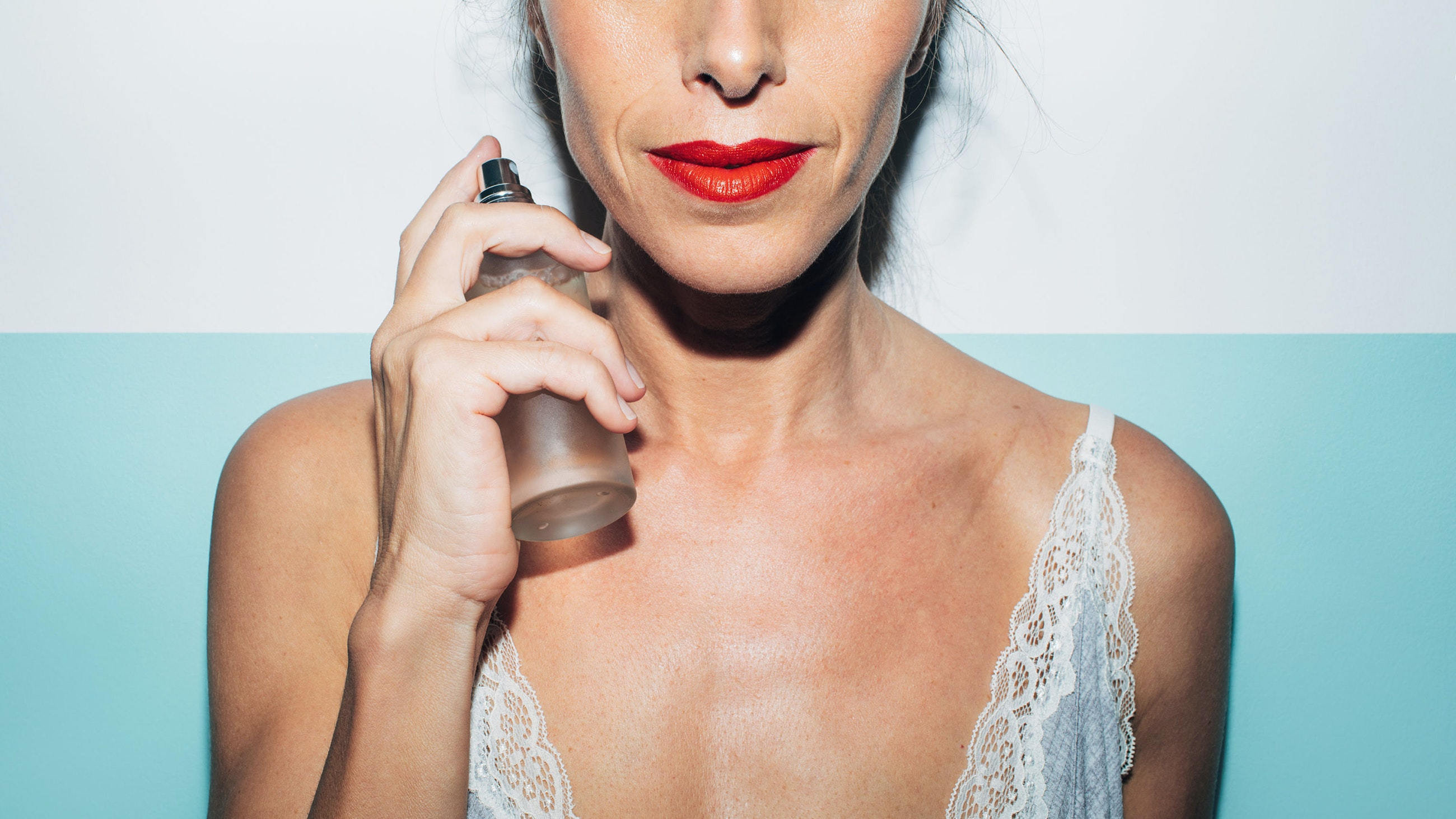 Portrait of an attractive woman in her fifties applying some perfume to her skin