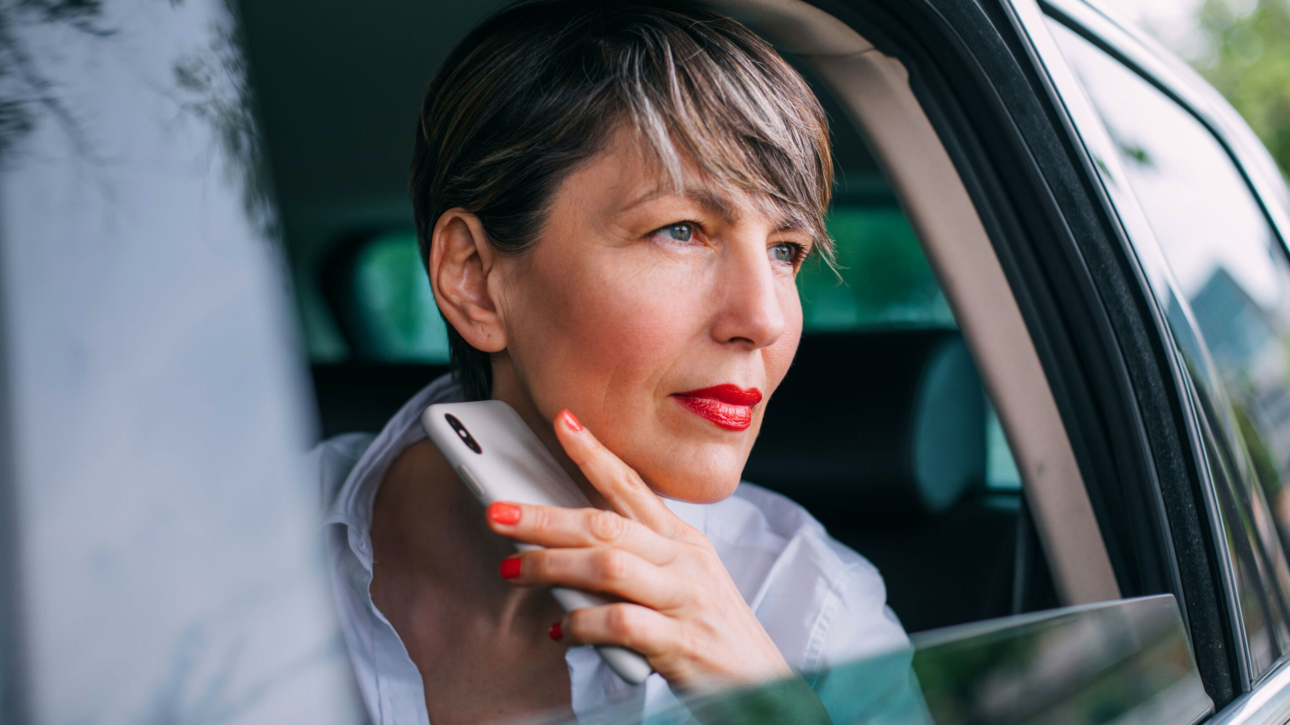 Beautiful middle aged businesswoman sitting in the car, looking through the window, holding a mobile phone