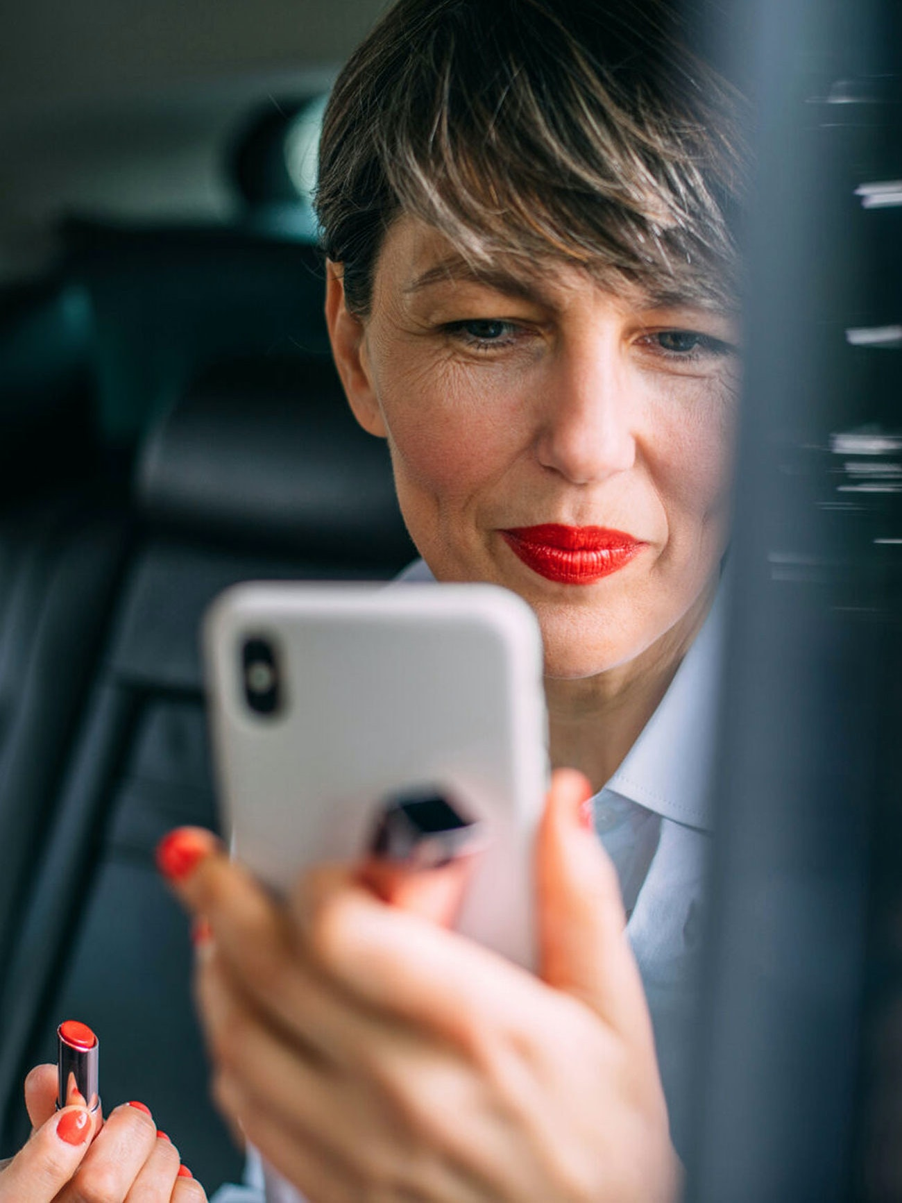 Portrait of a beautiful businesswoman putting lipstick in the car