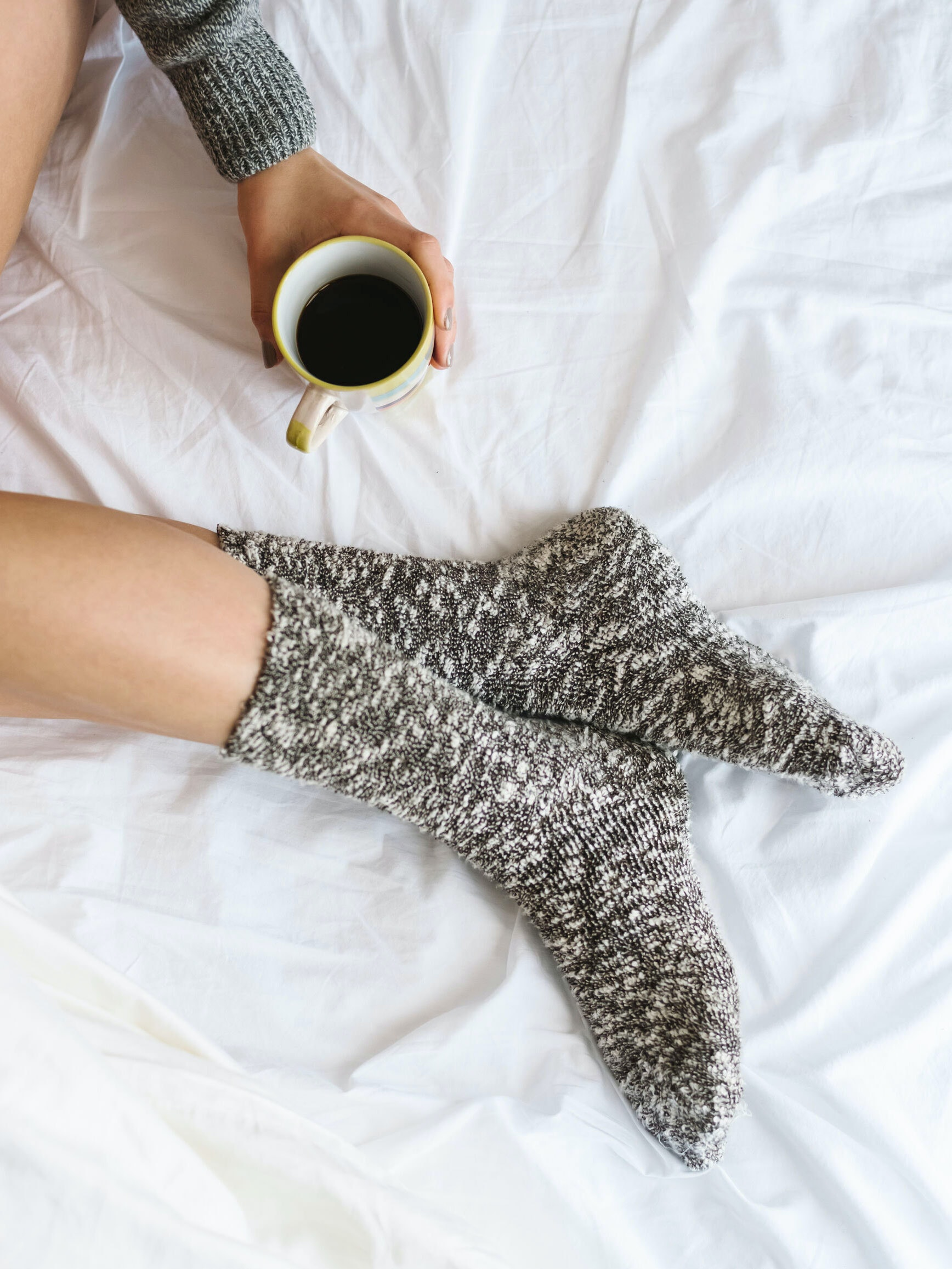 Person's feet wearing socks holding coffee