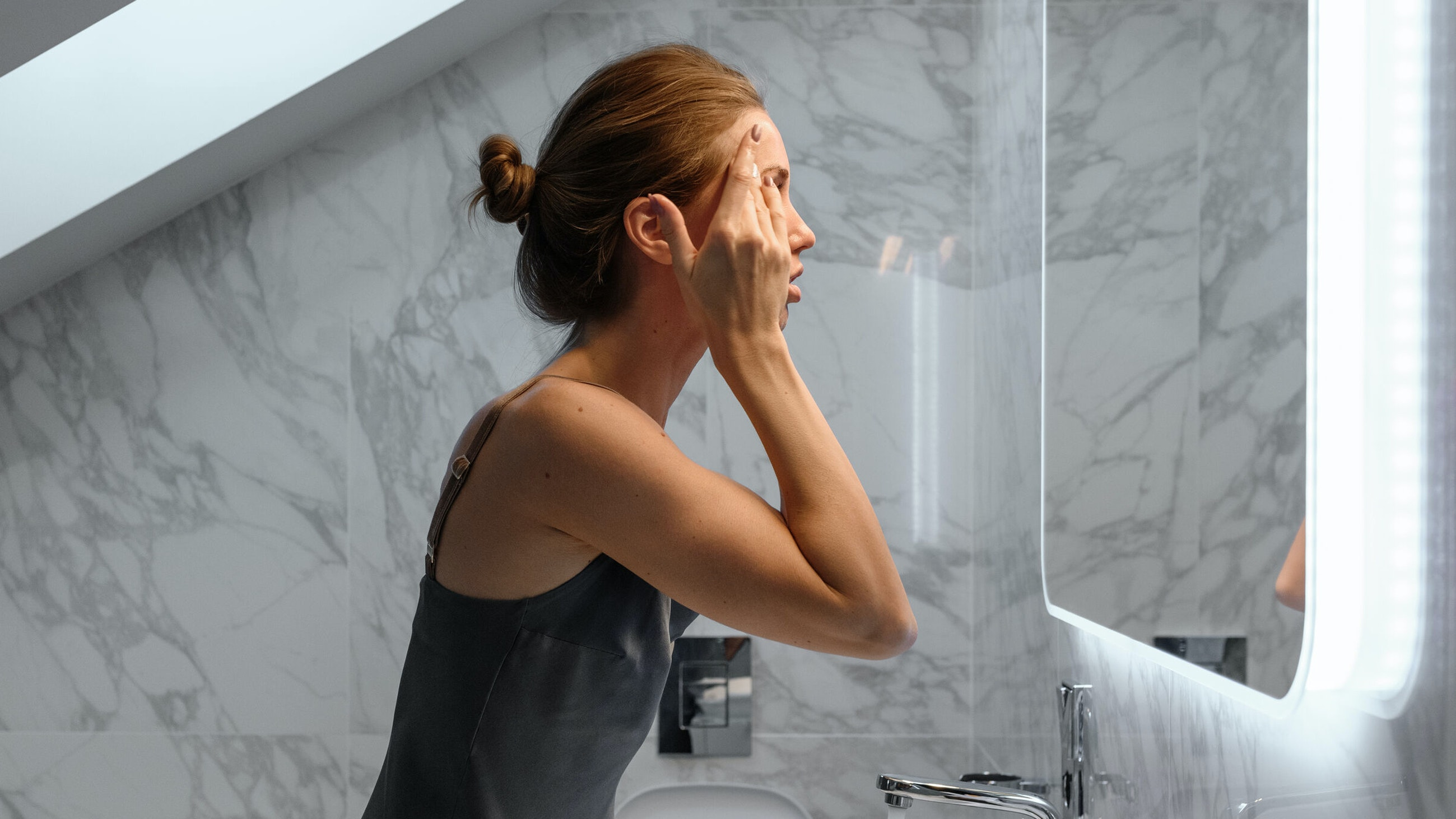 Woman treating rosacea in the mirror