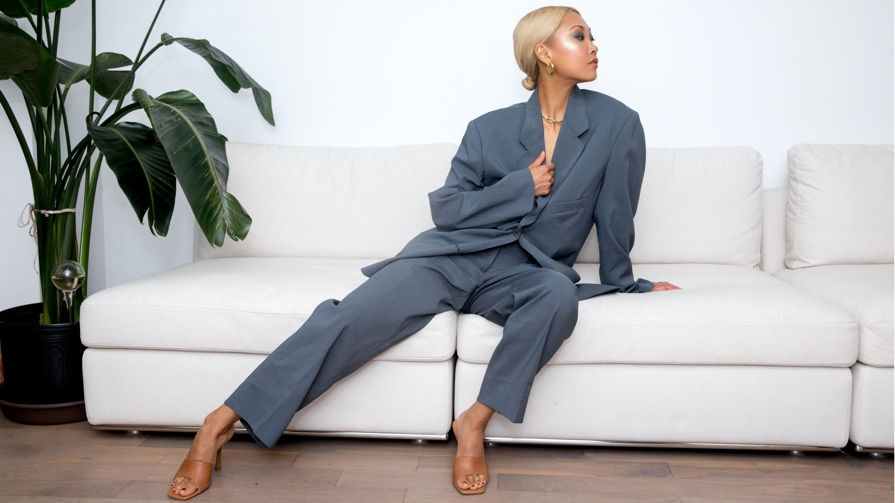 Vanessa Hong sitting on a couch wearing a Dior suit