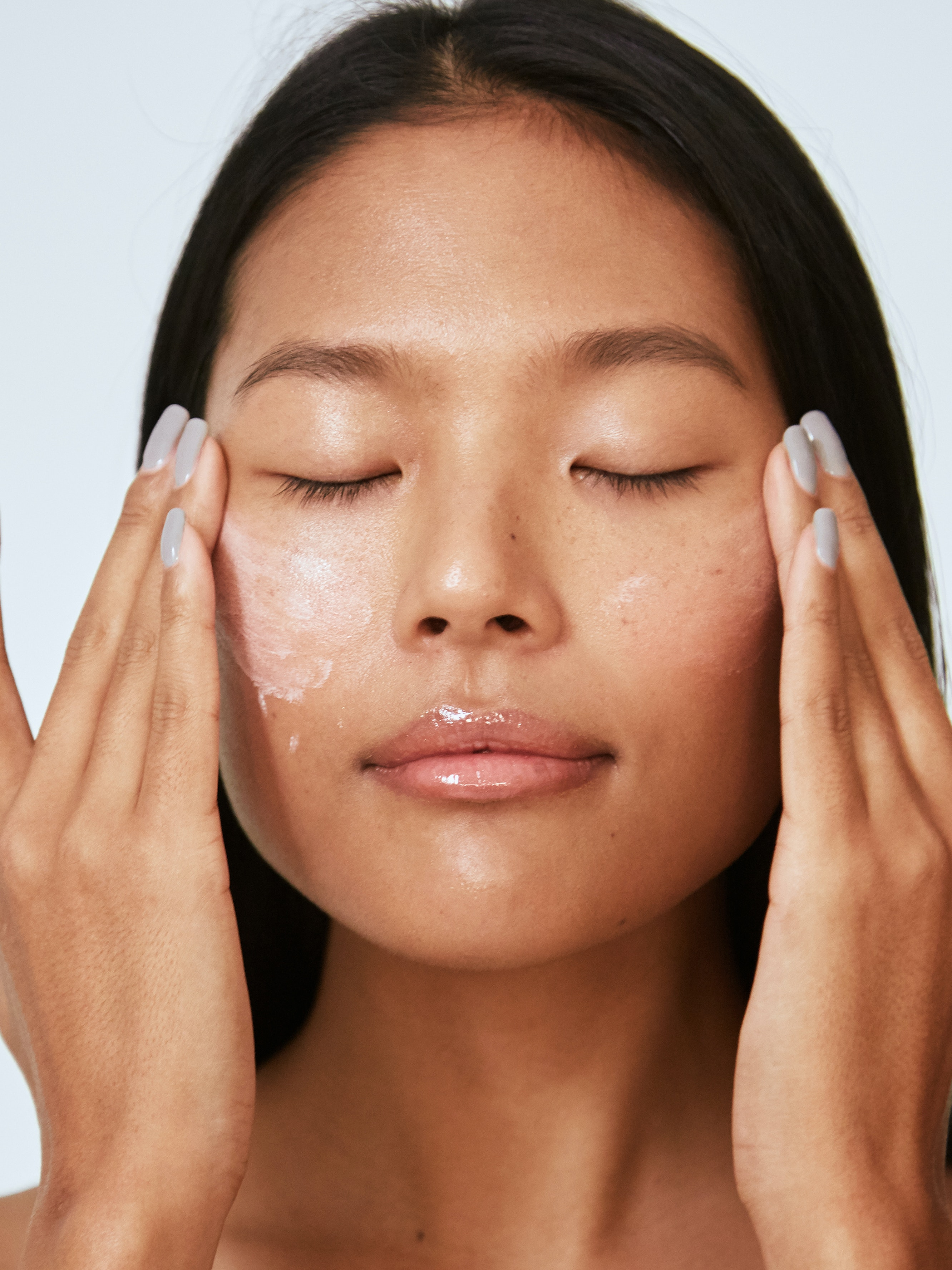 how to take care of your skin after aesthetic treatments woman applying skincare products to face