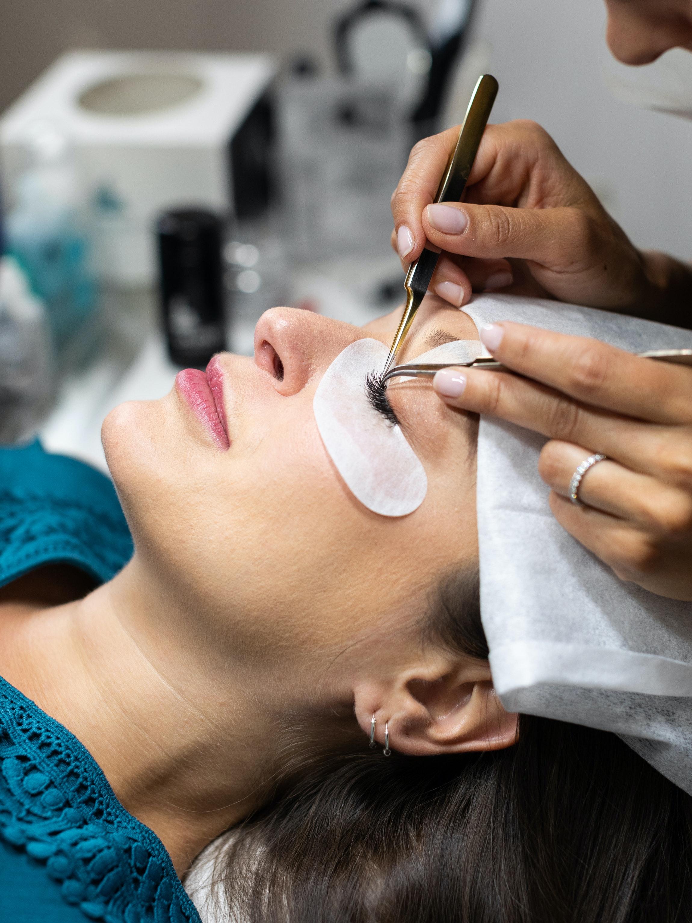 placing eyelash extensions onto woman