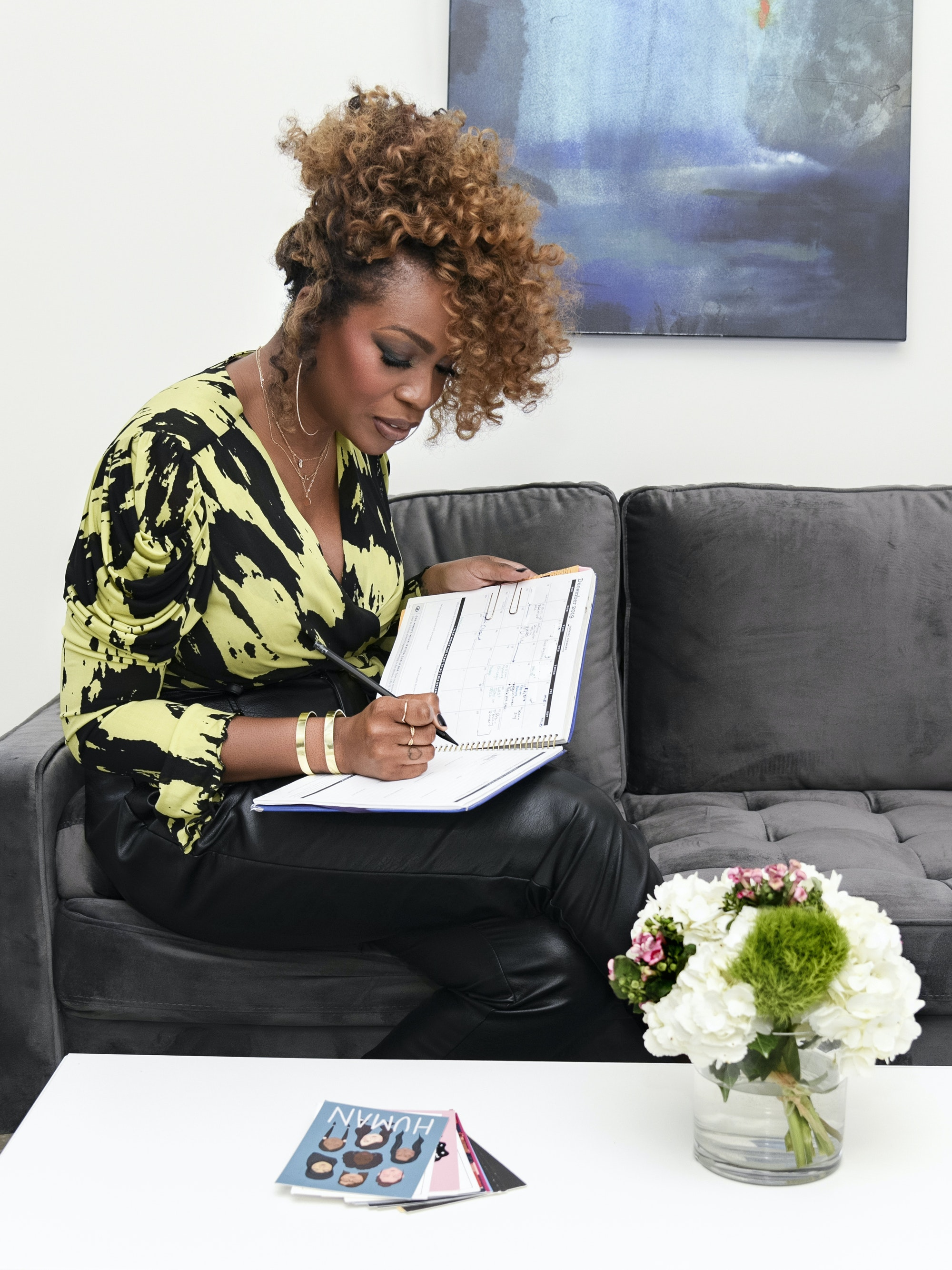 Beauty Publicist Liv Lewis writing in book green and black shirt