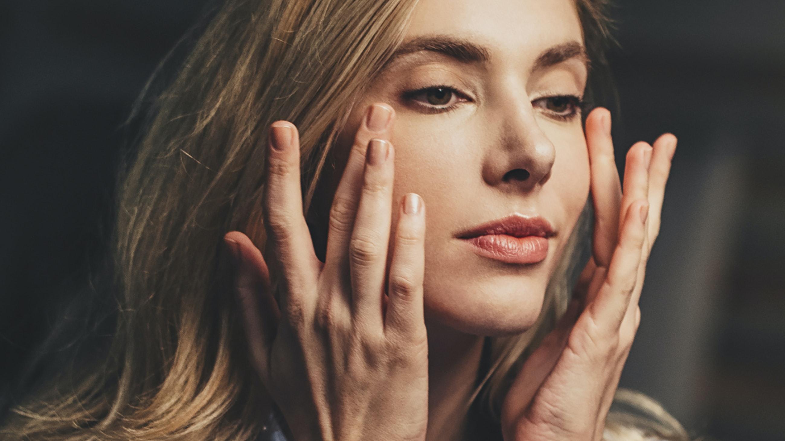 womaning touching cheeks