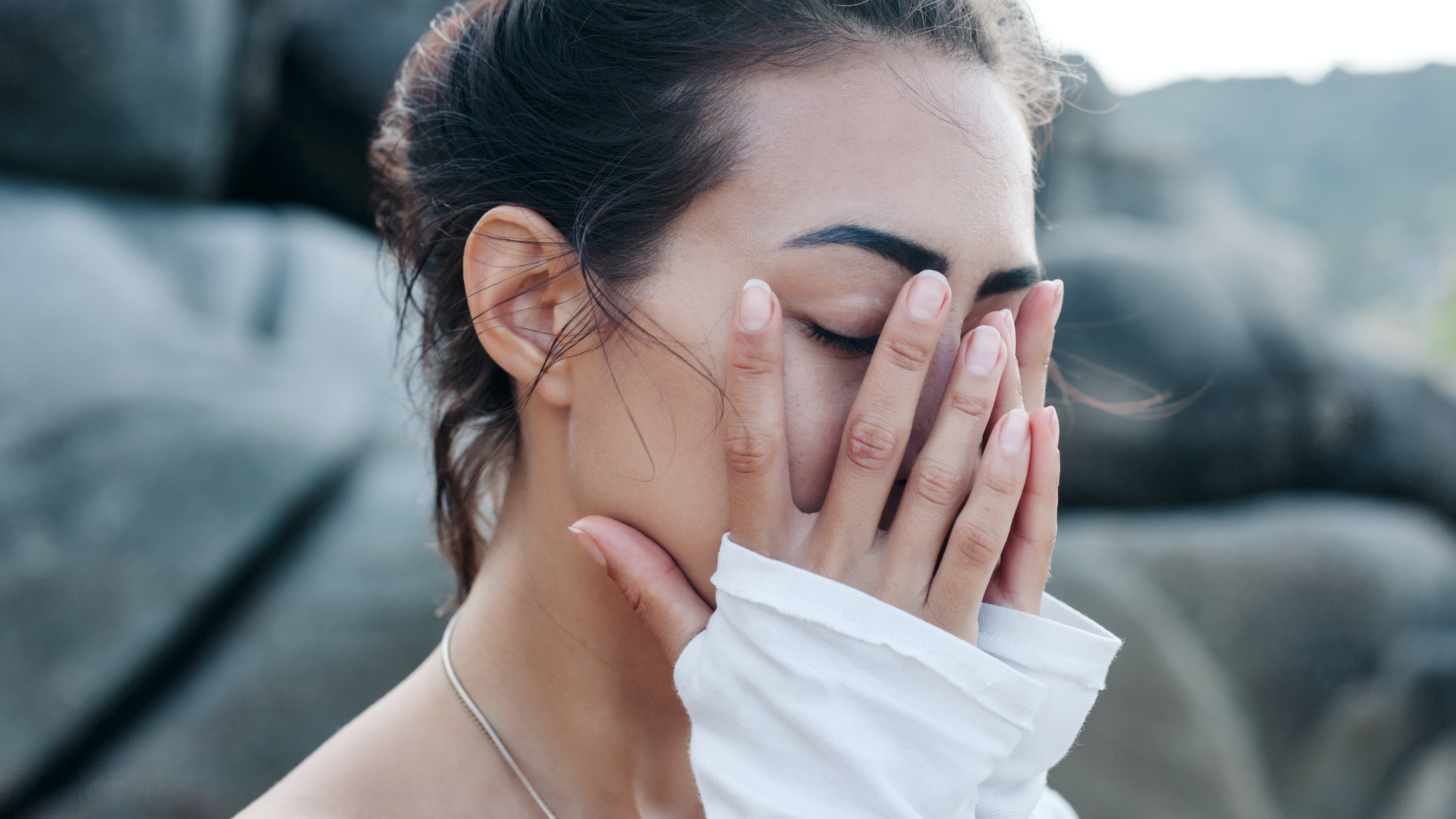 woman hiding her face with her hands covering milia bumps on face