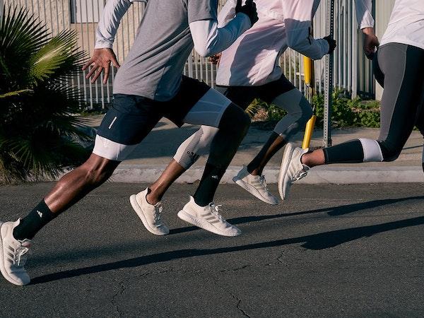 Three people running on the road wearing Adidas' FUTURECRAFT.Loop in white