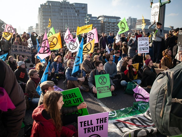 A group of Extinction Rebellion protestors occupy a bridge in London with colourful placards and posters