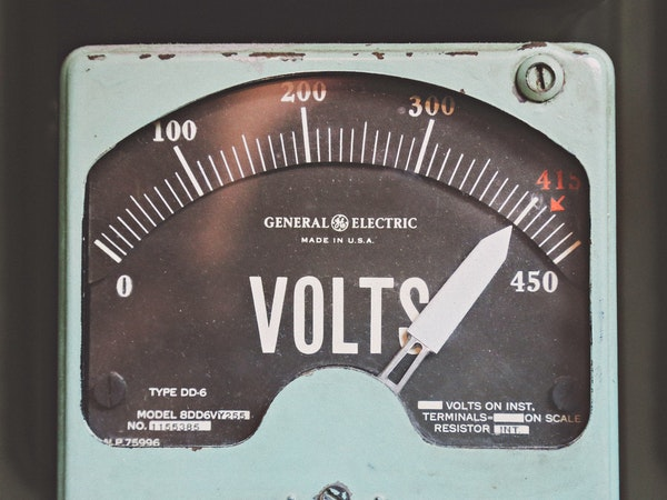 A photograph of a vintage, blue General Electric meter used to measure voltage