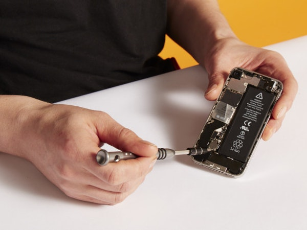 A person using a mini screwdriver to fix their smart phone